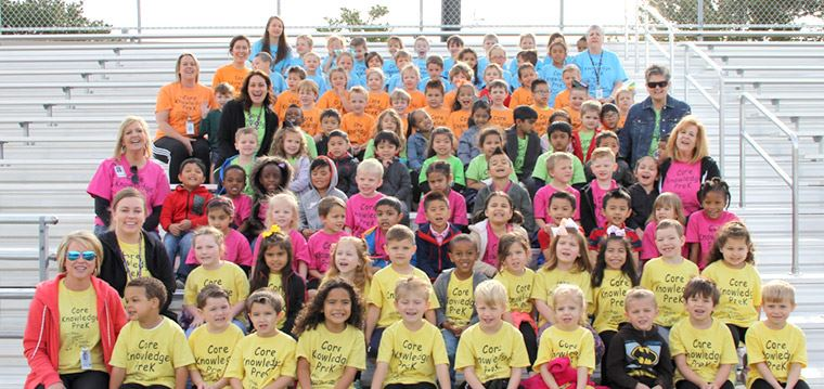 about 80 CK Pre-K students sitting on bleachers, wearing matching brightly colored shirts