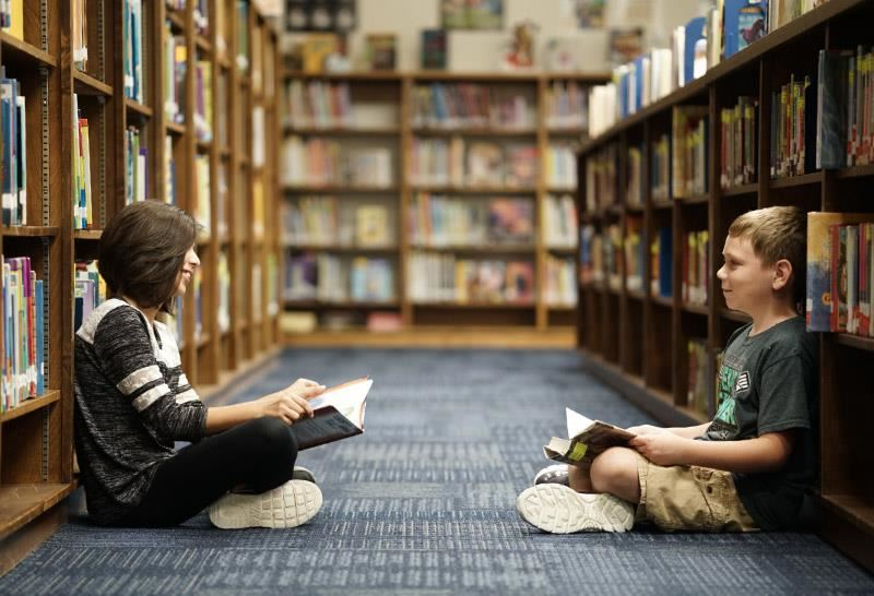 students reading on floor between library shelves