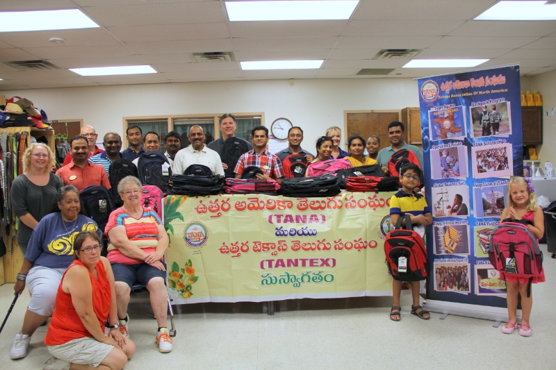members of Tantex organization behind a table covered with donated backpacks