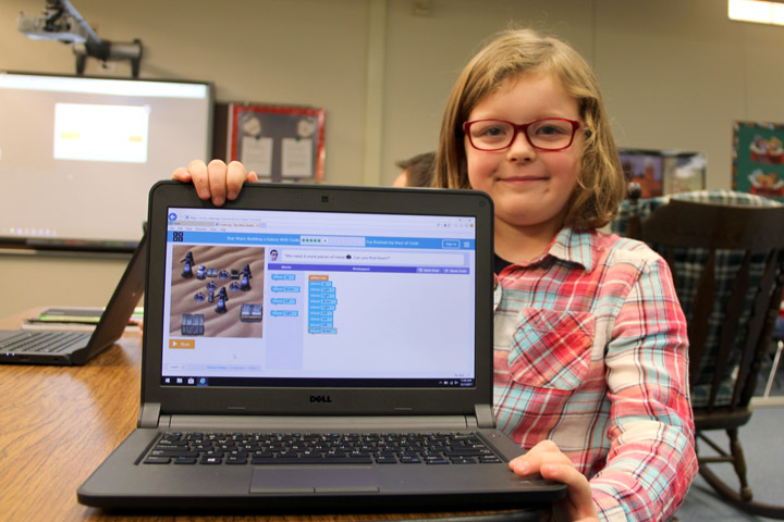 Student shows a laptop with Hour of Code activity in progress