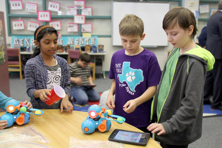 Students working with a robot programmed via tablet
