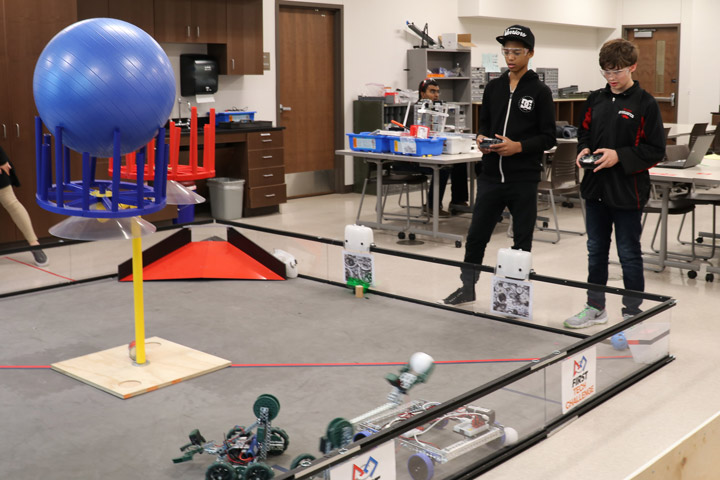 Students driving robots in competition arena