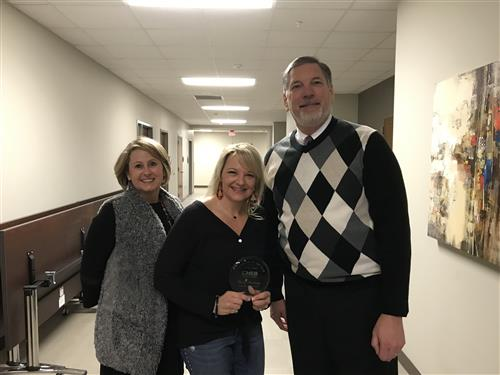 Rebecca Standridge holding award with Superintendent Steve Chapman and Assistant Superintendent of Elementary Administration