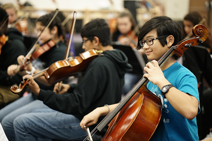 Junior high students playing string instruments