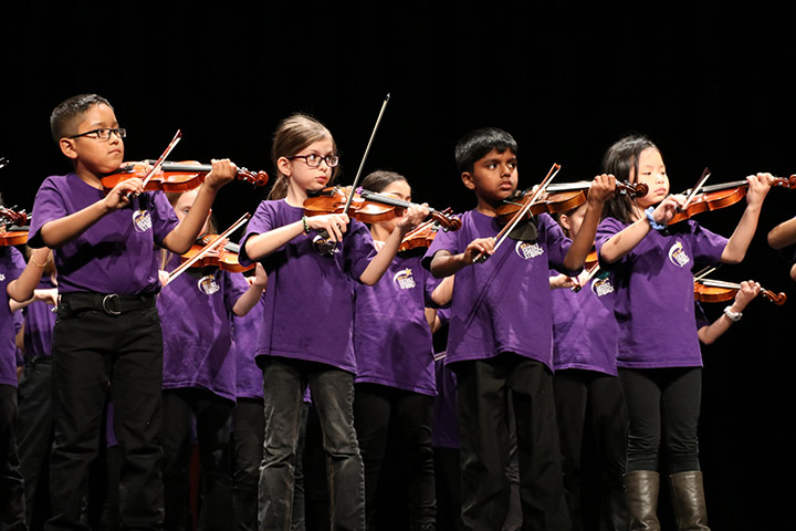 Young elementary students playing string instruments