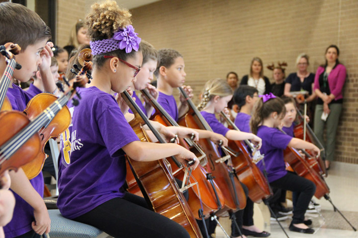 Elementary students playing cellos