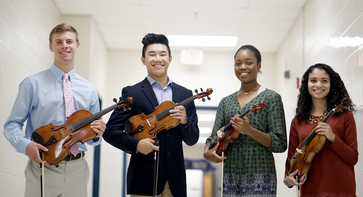 high school students holding violins