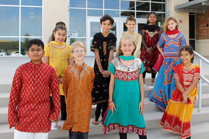 Students in traditional clothing outside a school