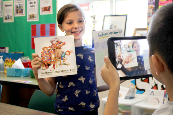 Student presenting a book written in Spanish