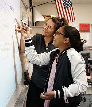 Student and teacher standing at SMART Board